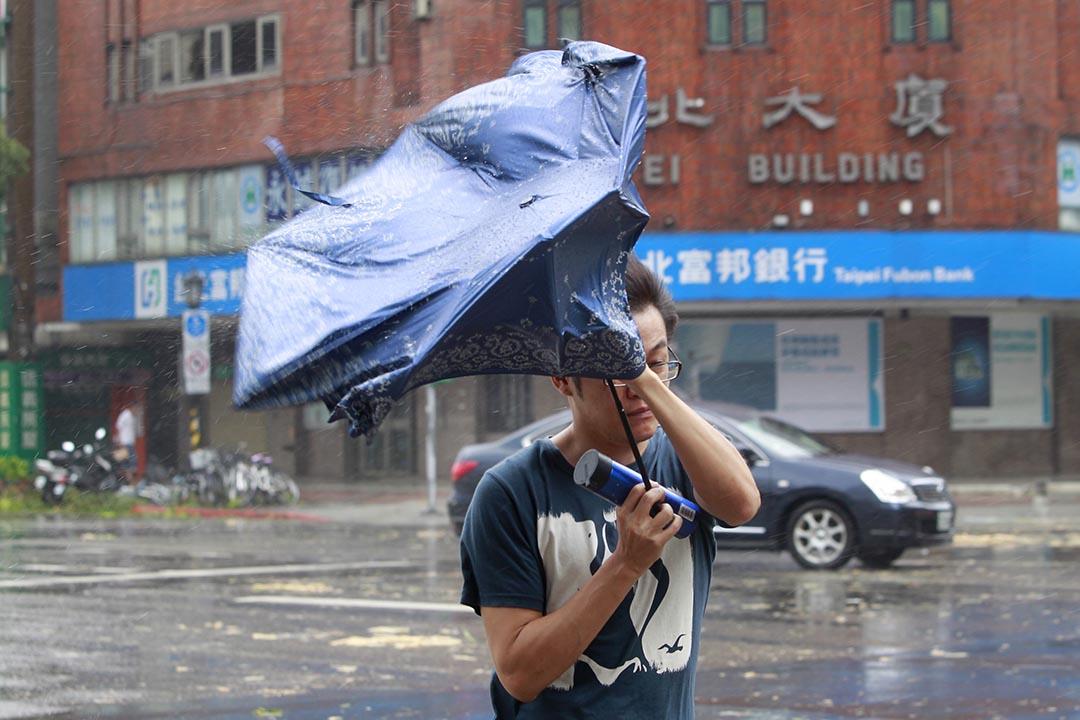 颱風蘇迪羅吹襲台灣,一名男子的雨傘被強風吹反。攝 : Chiang Ying-ying/AP