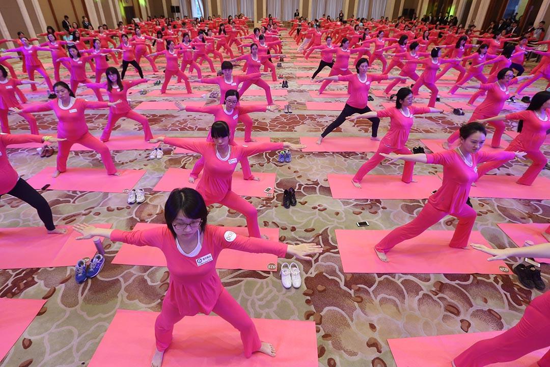2015年10月25日,北京,孕婦在釣魚臺國賓館練習瑜伽。全國一共1443名孕婦當天在中國不同城市做瑜伽,挑戰一天內有最多孕婦做瑜伽的健力氏世界紀錄。攝:CFP via GETTY
