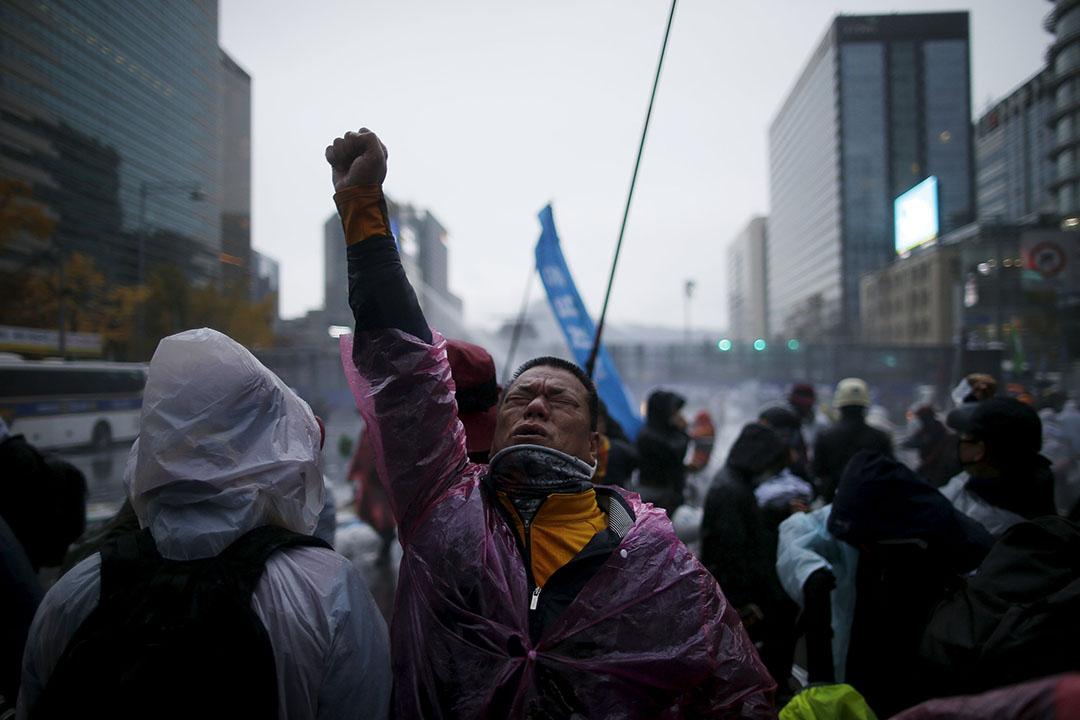 反政府示威者被警方的催淚水劑射中後高舉右手。攝:Kim Hong-Ji/REUTERS