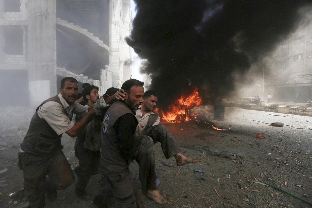 敘利亞平民搬運受傷者離開空襲現場。 攝 : Bassam Khabieh/REUTERS
