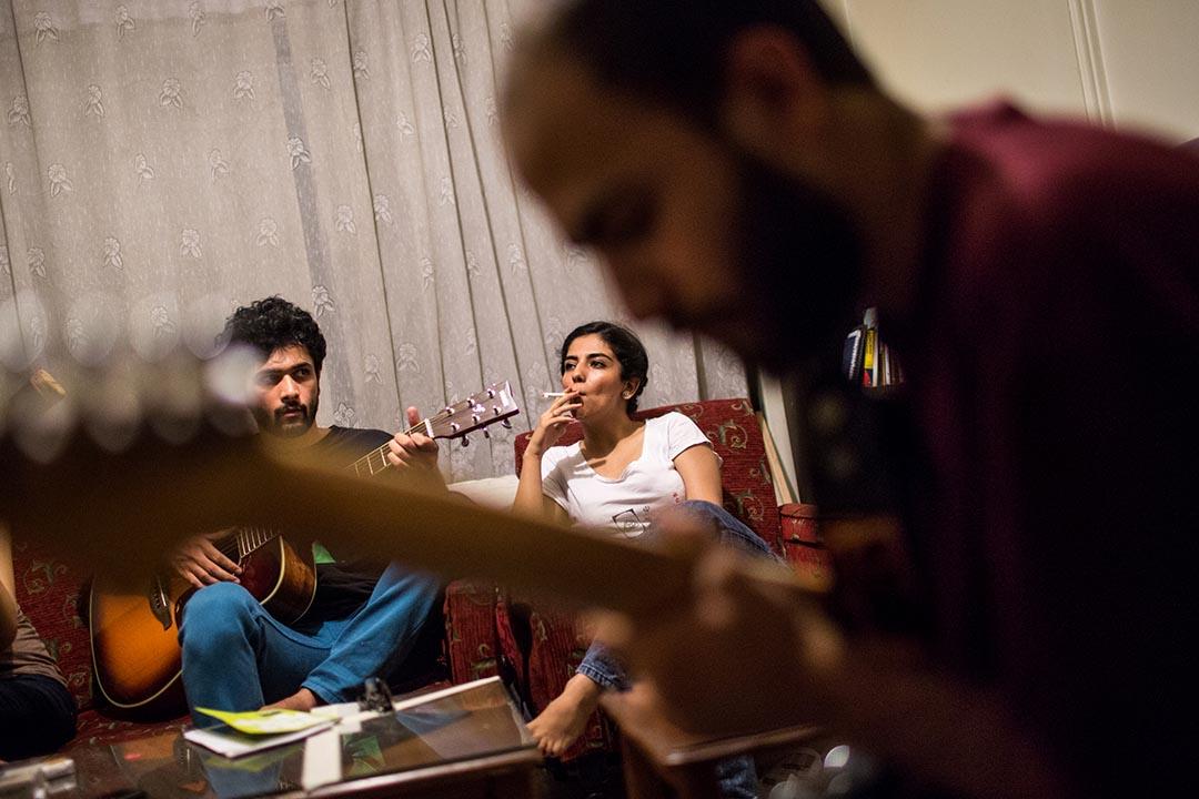 Melika,22歲,一個德黑蘭的蠟染學生。她正在聆聽她的畫家朋友 Mojtaba 和 Erfan 彈奏結他。攝:Arash Khamooshi/端傳媒