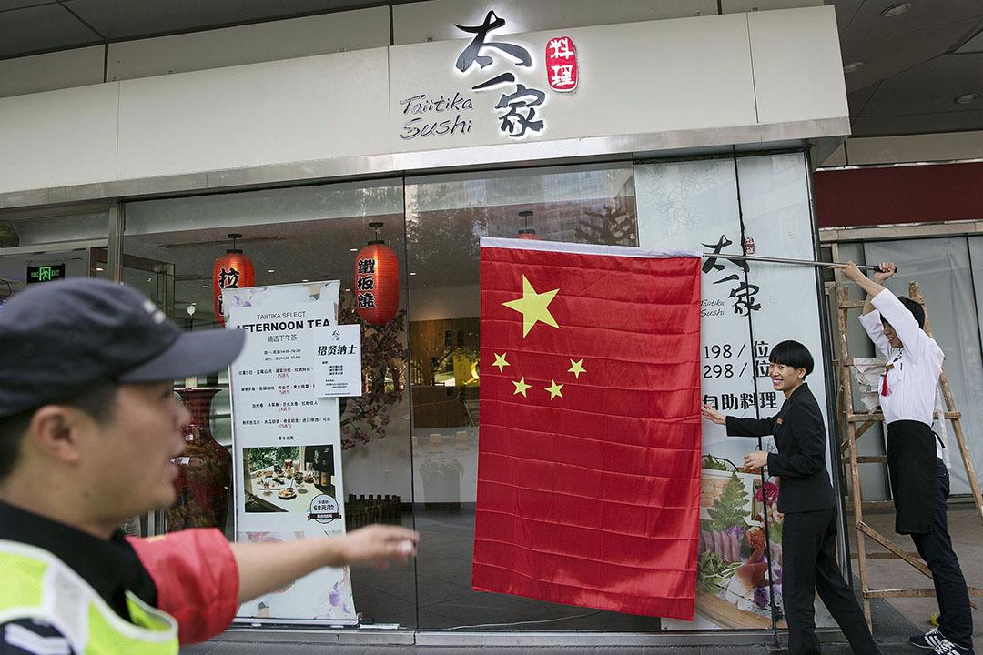 有市民在北京一間日本餐廳門外揮舞中國國旗。