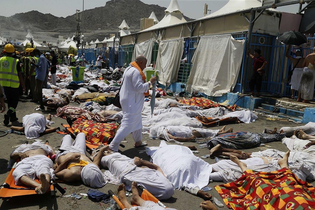 一名穆斯林朝聖者從屍體旁走過。攝 : AP
