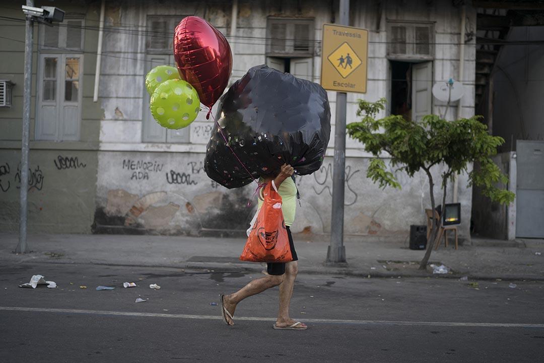 在巴西里約熱內盧,一個女人在嘉年華後,帶著氣球離開。攝:Leo Correa/AP Photo
