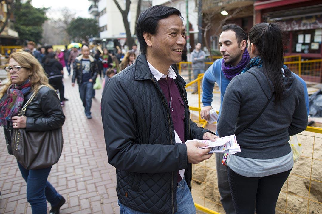 布市華人議員袁建平在散發國家方案黨總統候選人的傳單。攝:Anibal Greco/端傳媒