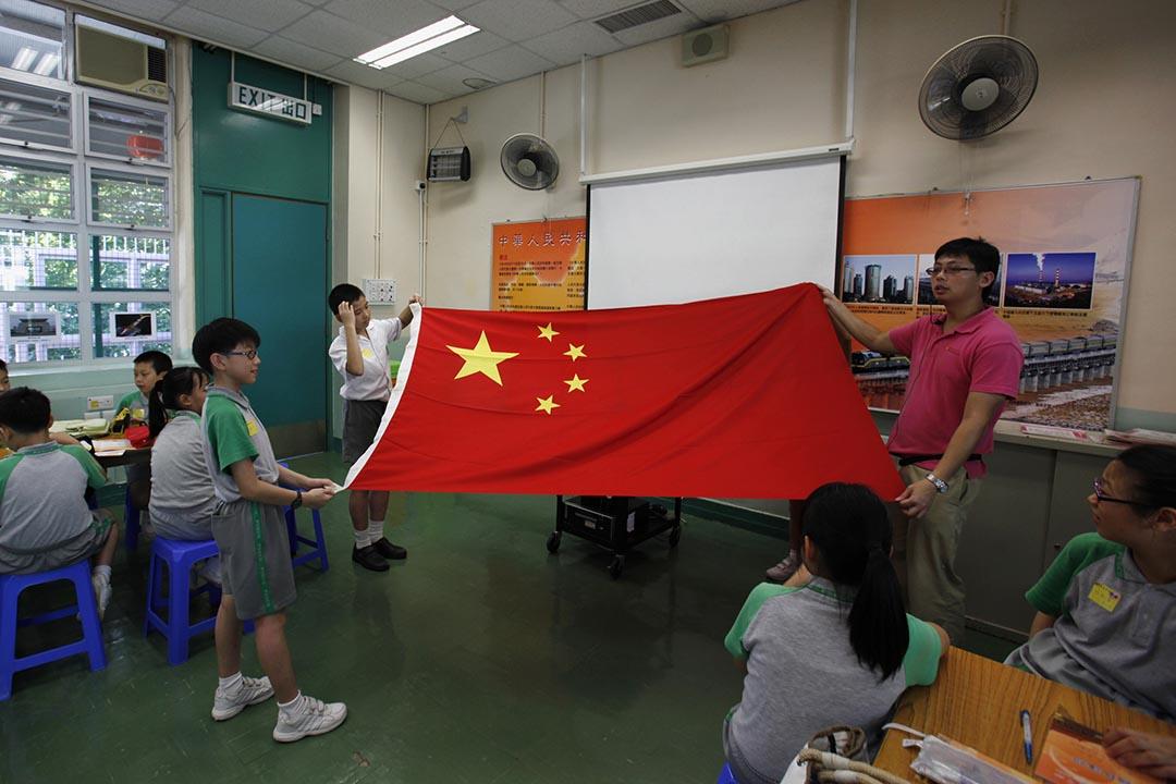 鄭司律:為什麼學生感情是可以被預期的?圖為香港小學生上課期間拉起國旗。 攝:Bobby Yip / Reuters