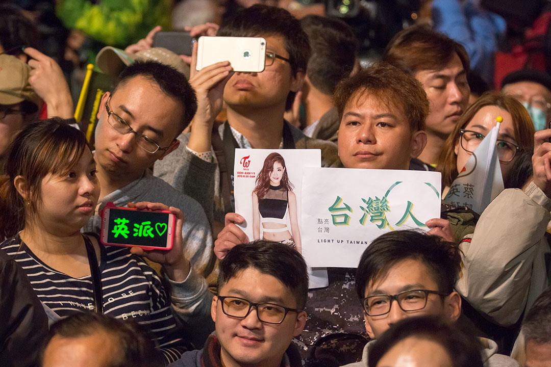 2016年1月16日,台北,蔡英文支持者在總統選舉後的勝選大會後高舉「台灣人」及台灣藝人周子瑜的照片。攝:張國耀/端傳媒