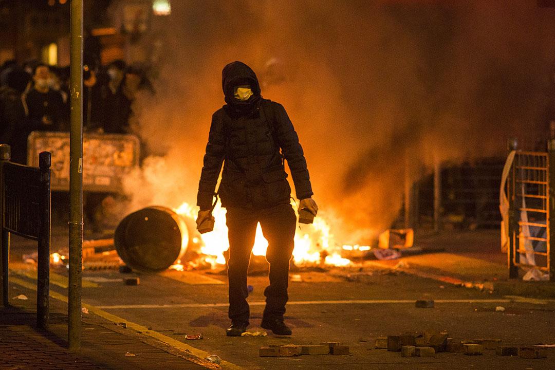 清晨5時,示威者在旺角通菜街手持磚塊。示威者背後為焚燒著的雜物。 攝: 林亦非/端傳媒