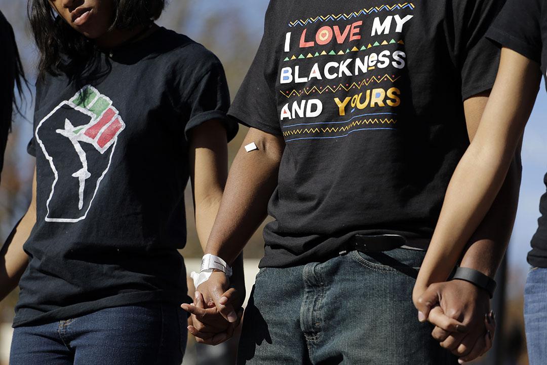 黑人研究生巴特勒(右)發起絕食抗議,要求校長請辭。在校長辭職後的一個集會中,巴特勒手腕上仍繫着醫院的繃帶。攝:Jeff Roberson/AP