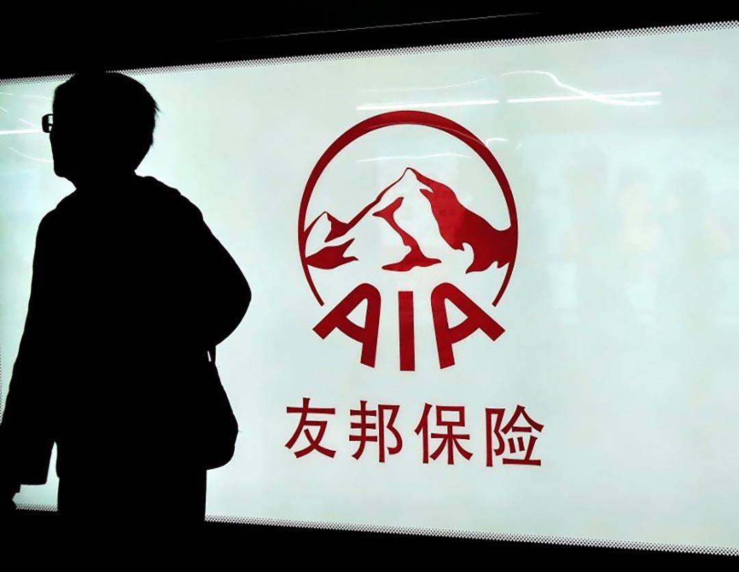 近年來,去香港購買保險的內地訪客在激增,保費屢創新高。圖為一名市民在友邦保險廣告前走過。攝 : Imaginechina