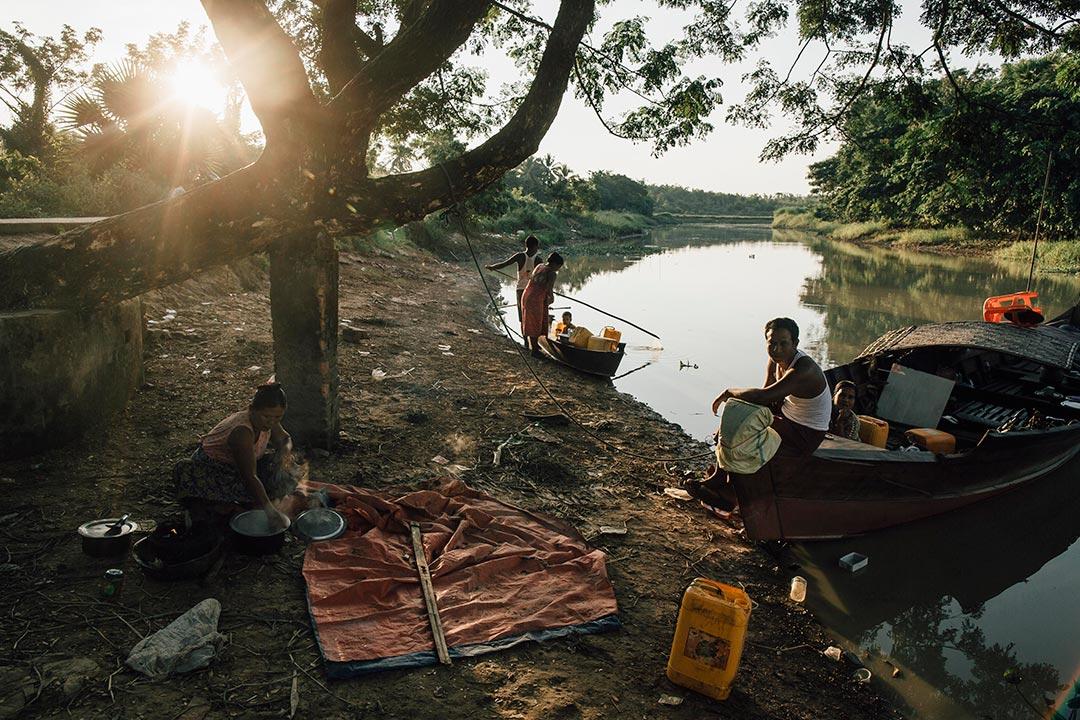 農民把船停泊在 Kaw Hmu 市集旁的河畔準備晚餐