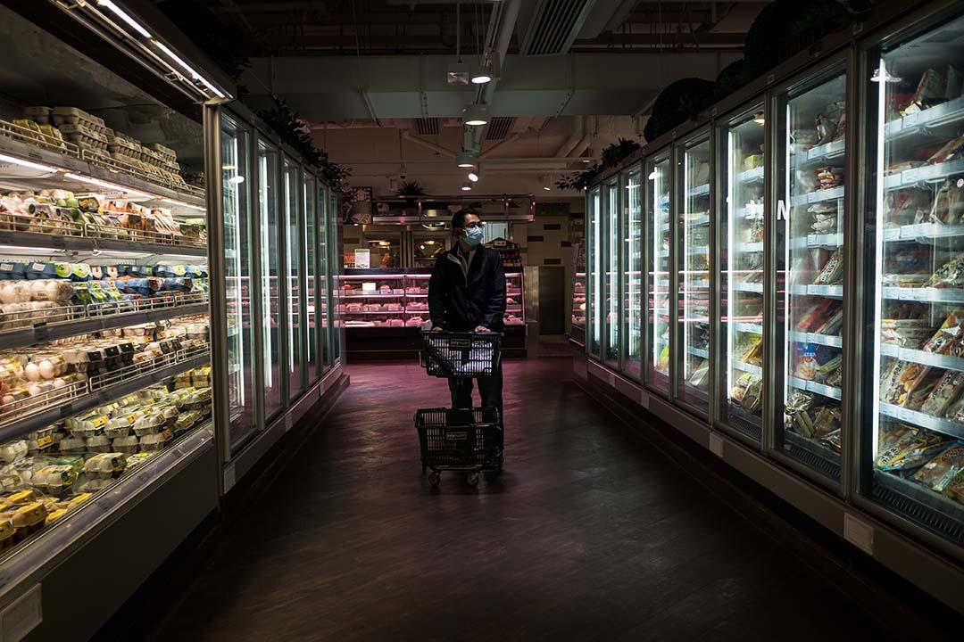 一名男士在超級市場選購食材。攝:Billy H.C. Kwok/端傳媒