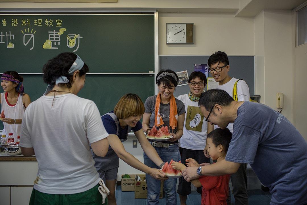 2015年8月23日 日本十日町市 香港農夫在越後妻有大地藝術展中的香港烹調工作坊內派發自己種植的西瓜。攝: Nicole Tung /端傳媒