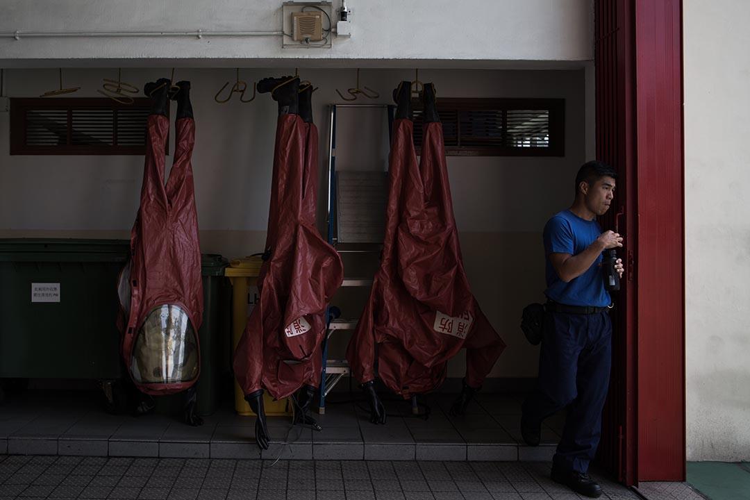 消防人員將 EVO 化學保護袍倒掛瀝乾。攝:盧翊銘/端傳媒
