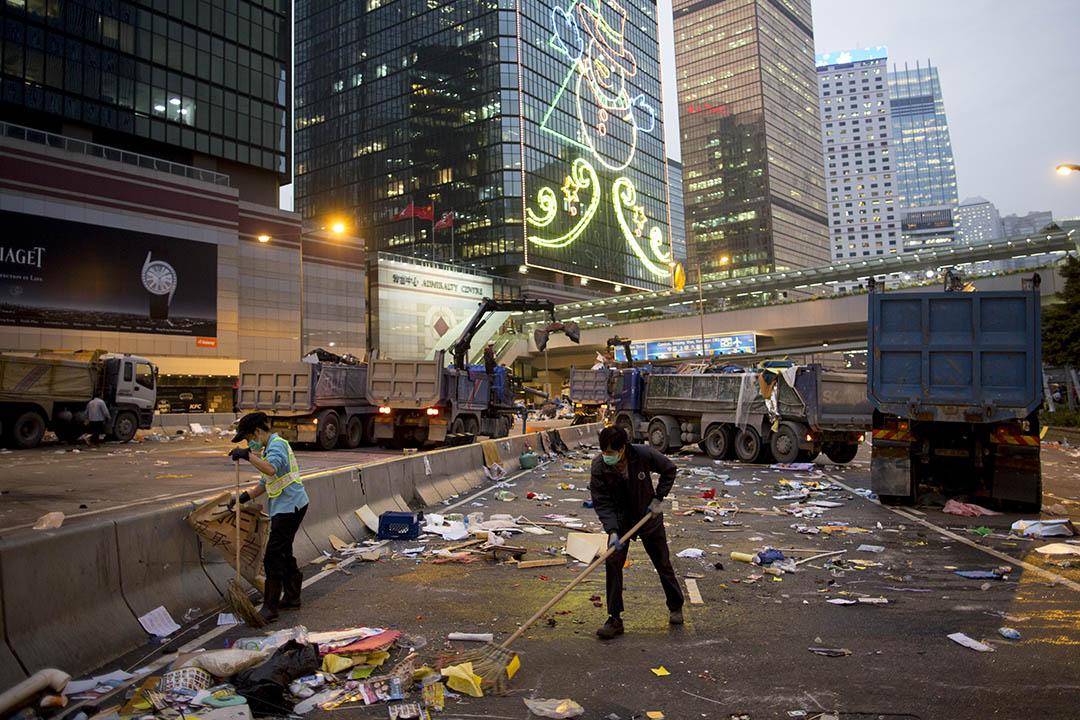 2014年12月11日,香港金鐘,佔領運動被清場後,清潔工人在夏愨道清理馬路上的雜物。攝:Brent Lewin/GETTY