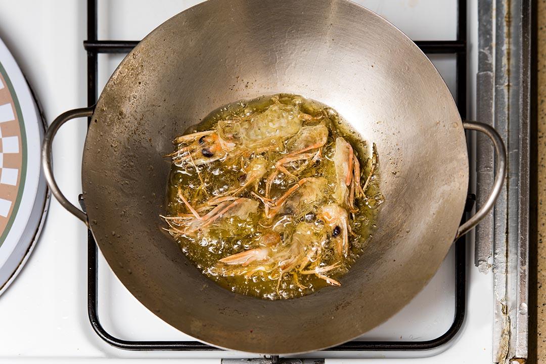 在小鍋下一杯橄欖油,以小火先炸香蝦頭,後下蝦殼,然後盛起蝦頭,撒幼海鹽供食。攝:LIT MA/端傳媒