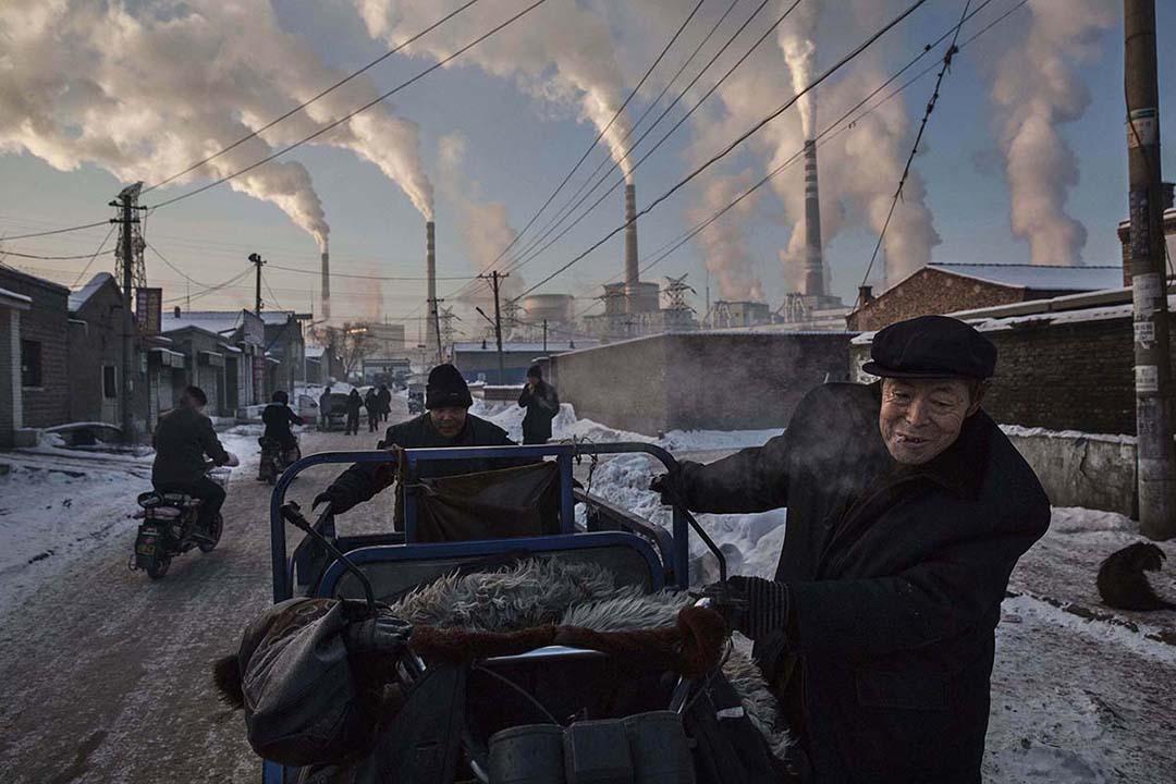 2015年11月26日,中國,兩名男士在一所燃媒工廠附近拉著一輛三輪車。攝:Kevin Frayer/GETTY
