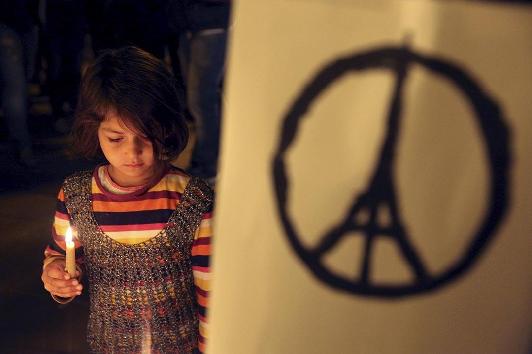 2015年11月15日,塞浦路斯,一名女孩手持燭光悼念法國恐襲案中的死難者。攝:Yiannis Kourtoglou/REUTERS