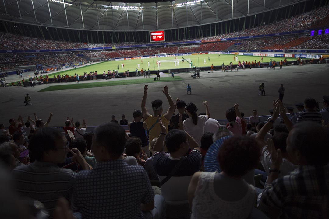 隨同鄉會到場觀賞球賽的群眾看見香港隊龍門的表現,振臂高呼。 攝 : 葉家豪/端傳媒