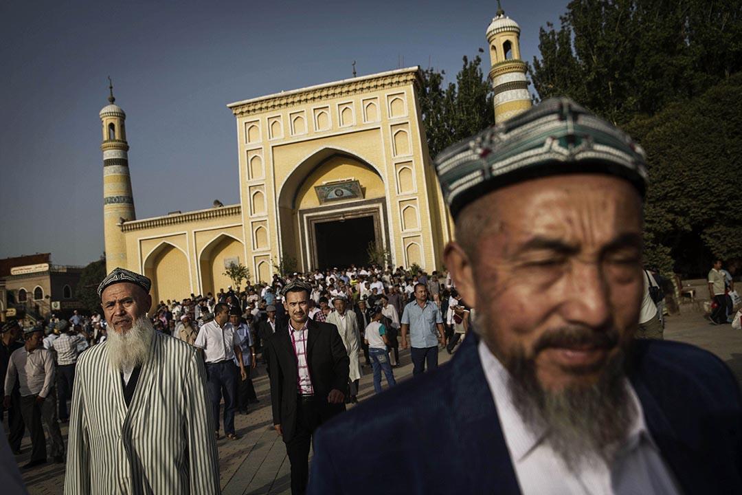 2014年7月29日 維吾爾族男人從新疆喀什艾提尕爾清真寺前走過。攝: Kevin Frayer/GETTY