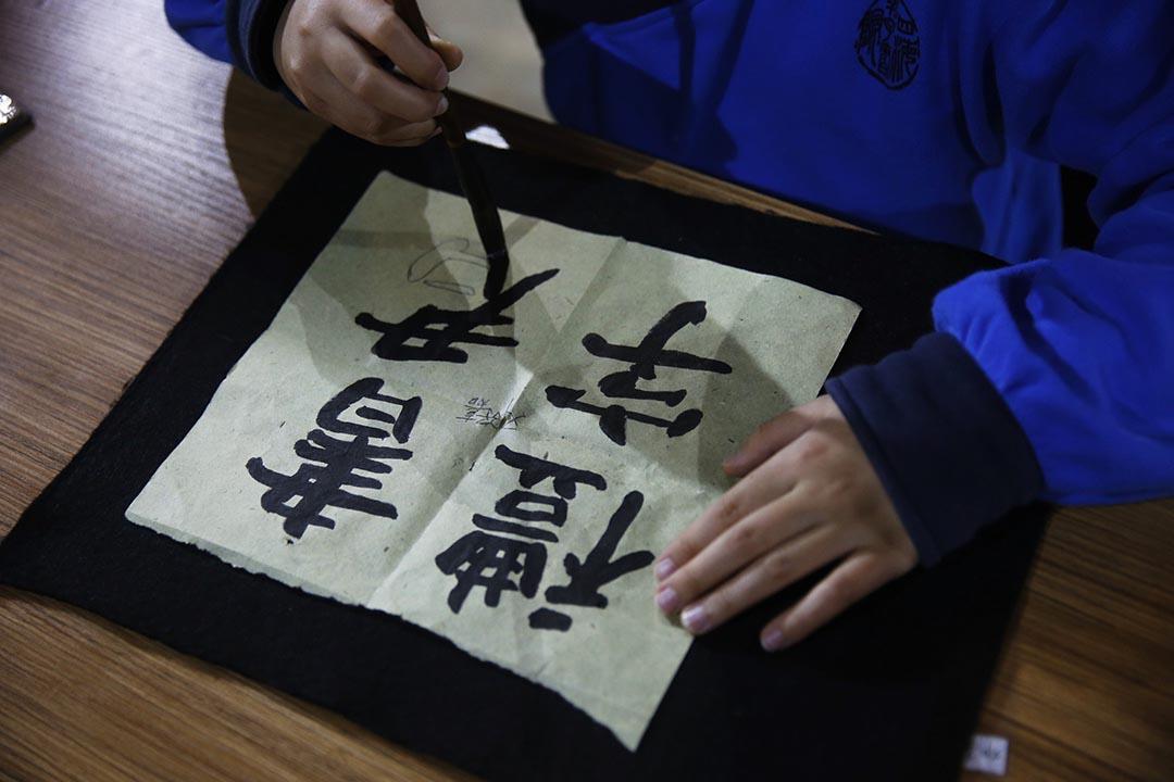 學生正在論語堂內練習書法。攝:Wu Hao/端傳媒