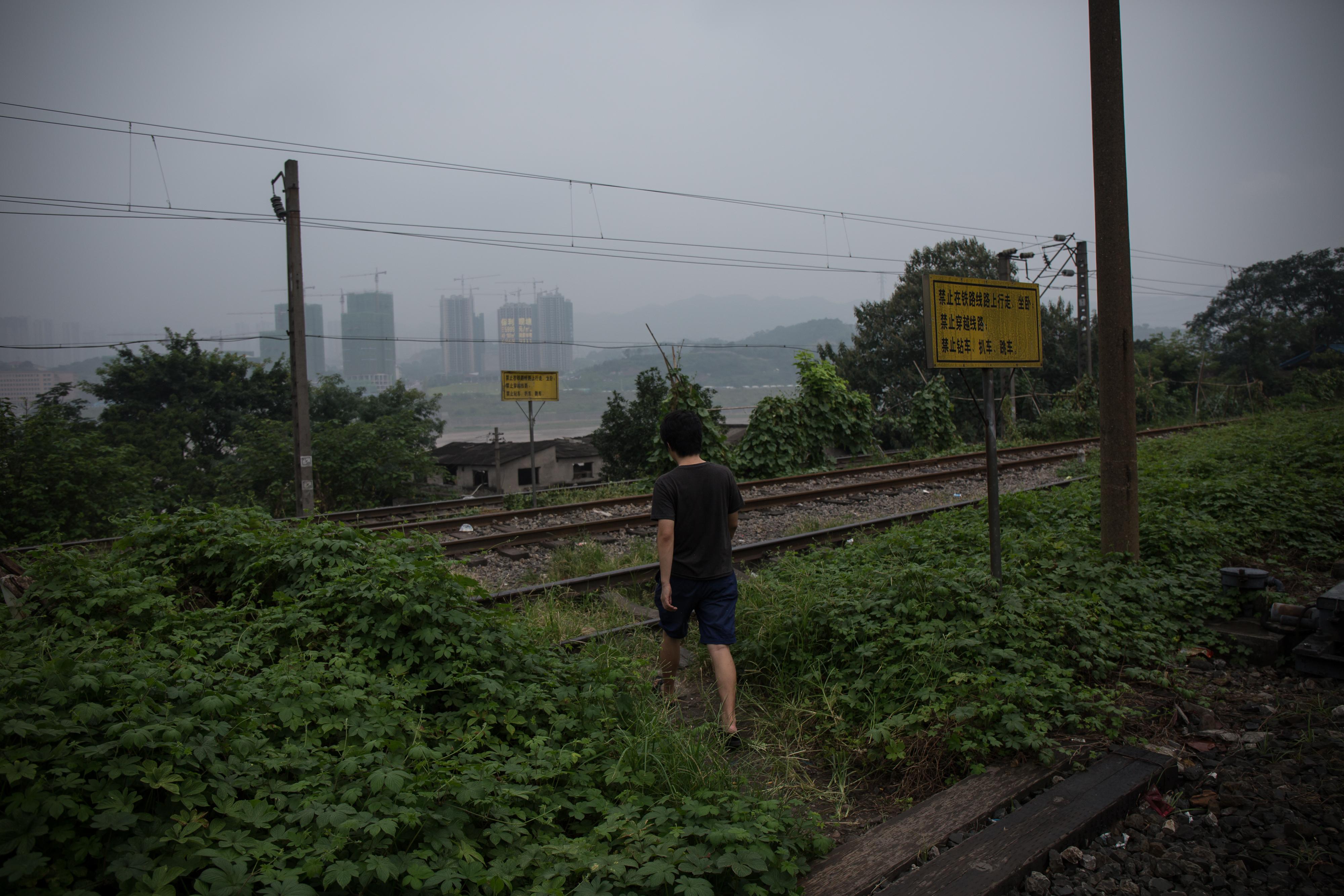 劉偉偉走過火車路軌。攝: Billy H.C. Kwok/ 端傳媒