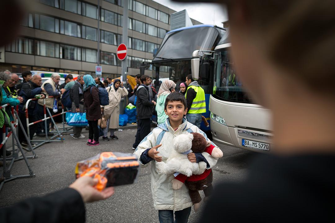 2015年9月6日,德國慕尼克,難民經匈牙利入境歐洲後抵達慕尼黑中央車站。圖為一名難民小童領取由義工送贈的禮物。攝:Gordon Welters/端傳媒