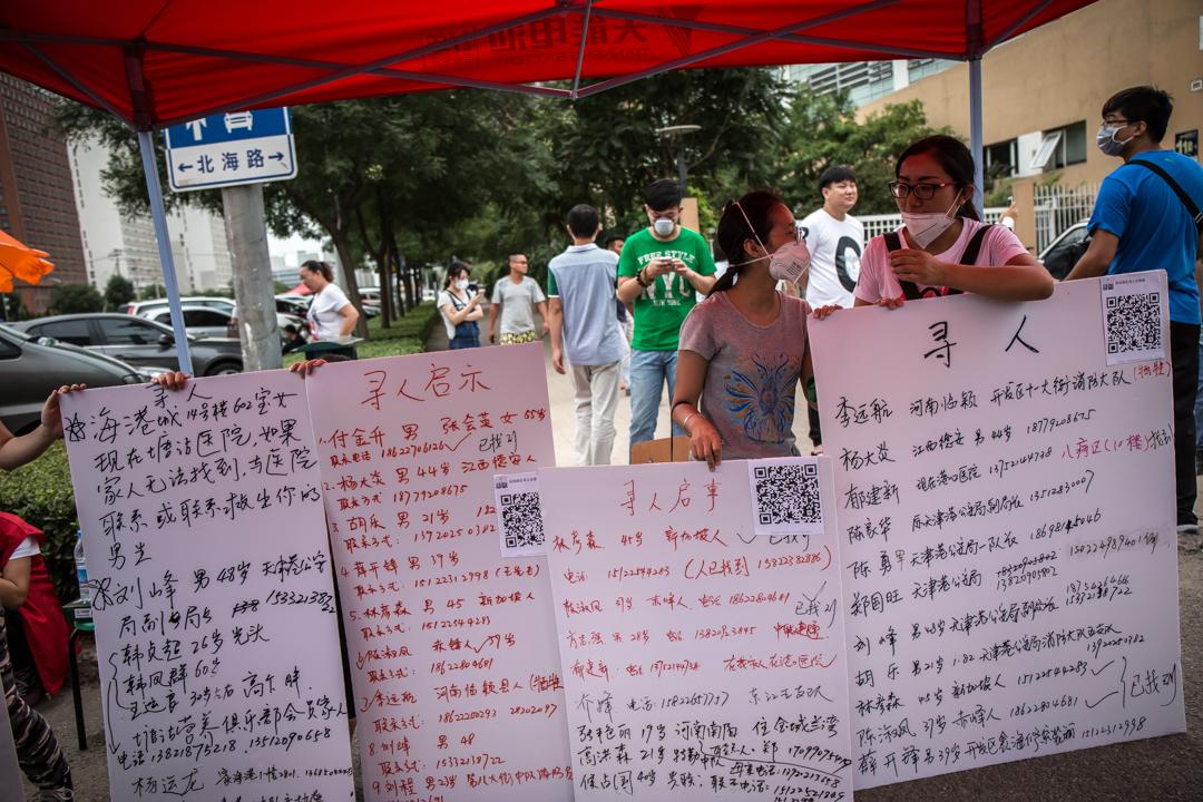 當地居民在紙板上寫上失縱親友的聯絡方法。