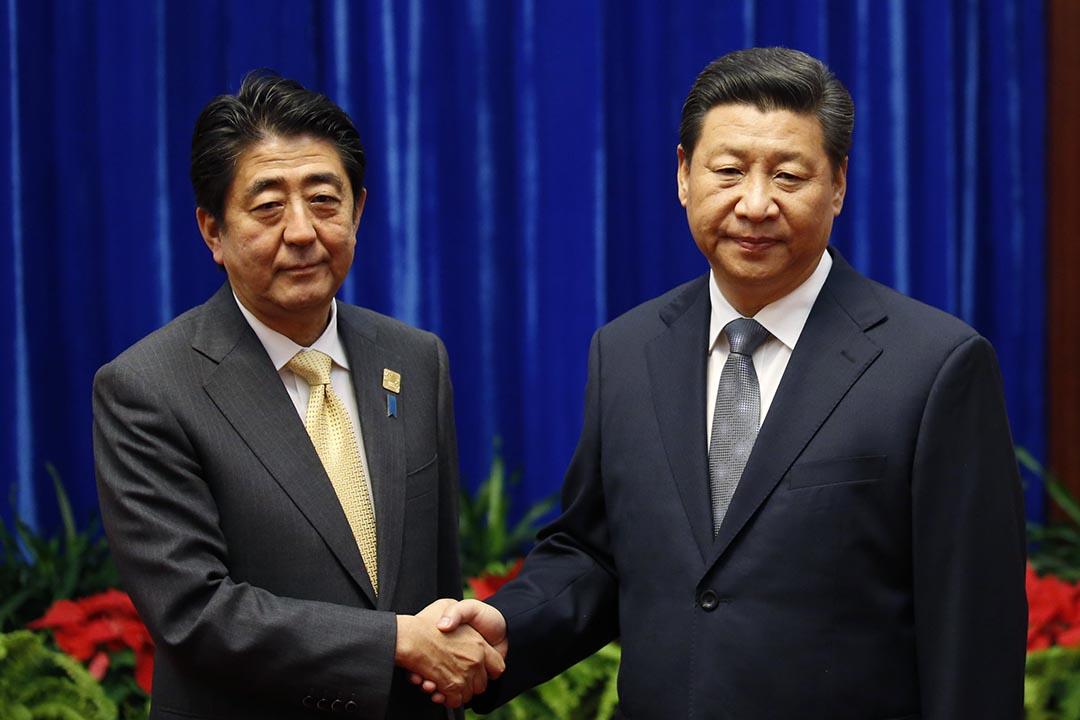 2014年11月10日,中國主席習近平與日本首相安倍晉三在亞太經合組織會議(APEC)上互相握手。攝:Kim Kyung Hoon/GETTY