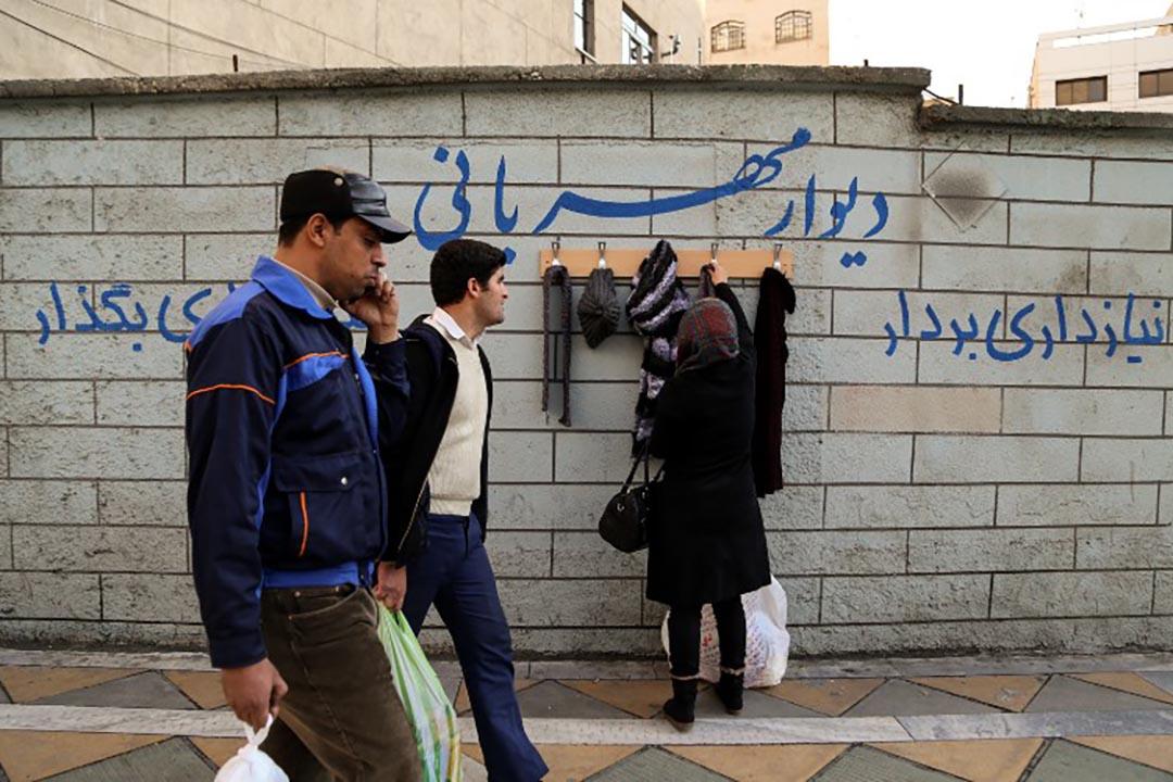 一名伊朗市民在愛心牆拿起一件衣服。攝 : Fatemeh Bahrami/Anadolu Agency