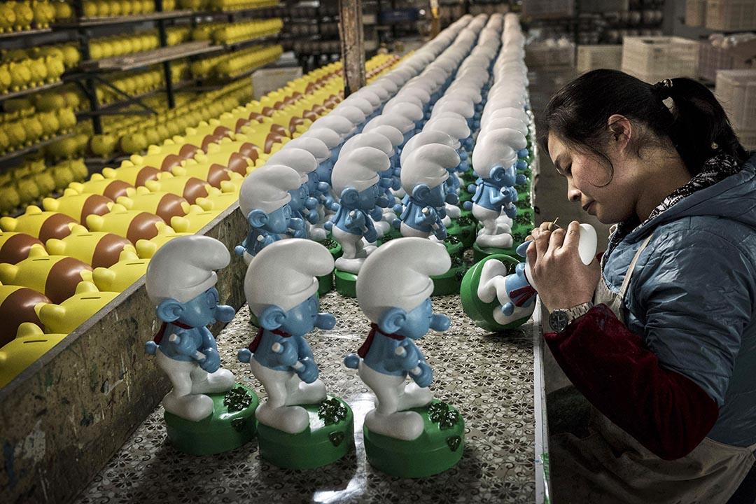 中國福建省的女工在工廠中為藍精靈模型塗上漆油。攝:Kevin Frayer/Getty