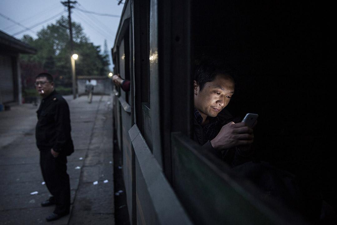 四川省石溪一名男子在火車上看手機。攝:Kevin Frayer/Getty