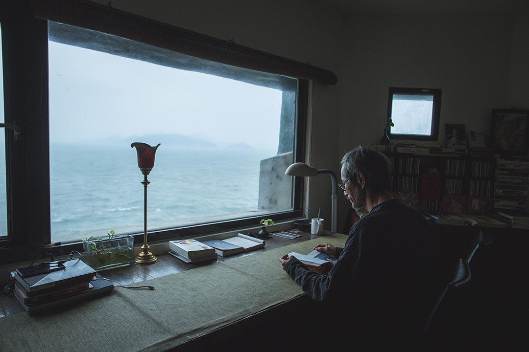 面向海邊,在書房看書的刺鳥咖啡館負責人曹以雄。攝:王嘉豪/端傳媒