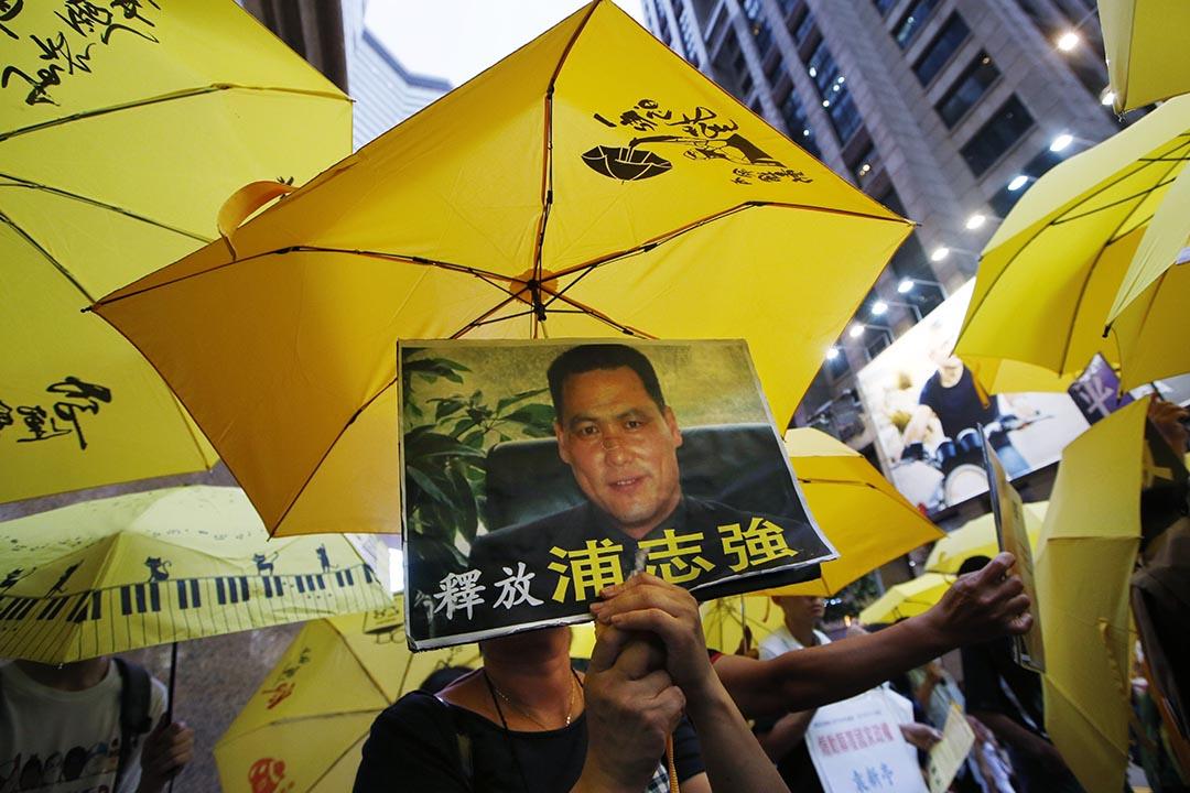 2015年7月23日,香港,市民手持浦志強頭像示威牌,要求中國當局釋放數十名維權律師。攝:Kin Cheung/AP