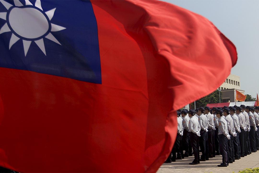 台灣國家安全局人員在台灣旗幟下。攝:Pichi Chuang/REUTERS
