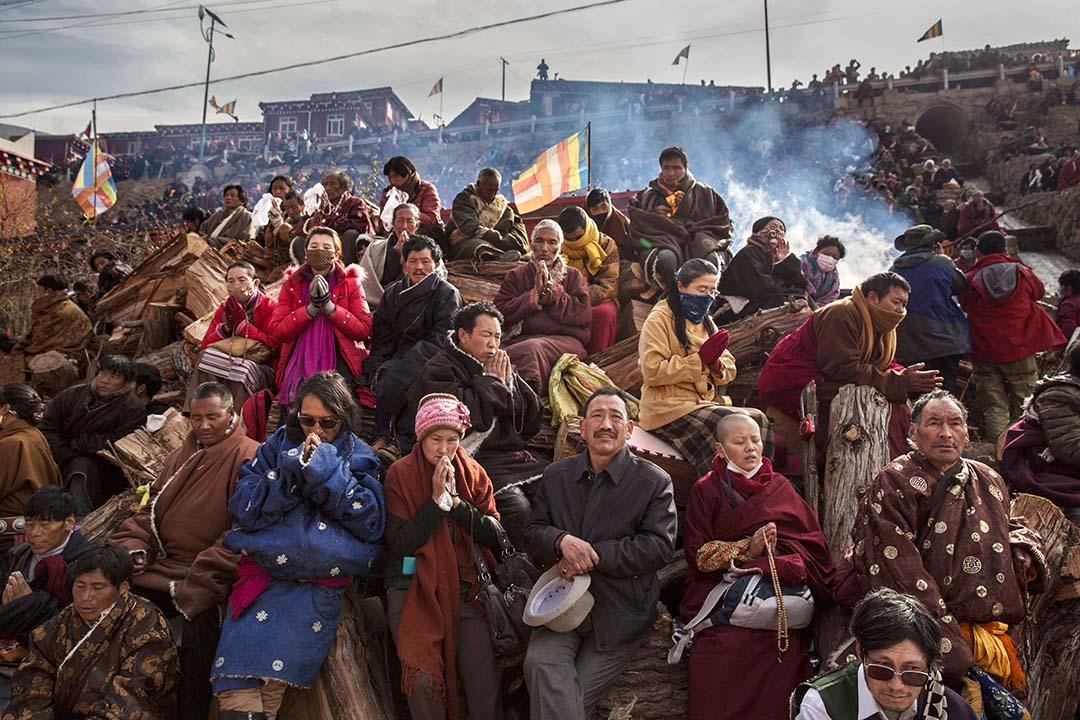 2015年10月30日,藏傳佛教教徒在山坡上誦經祈禱。攝:Kevin Frayer/Getty