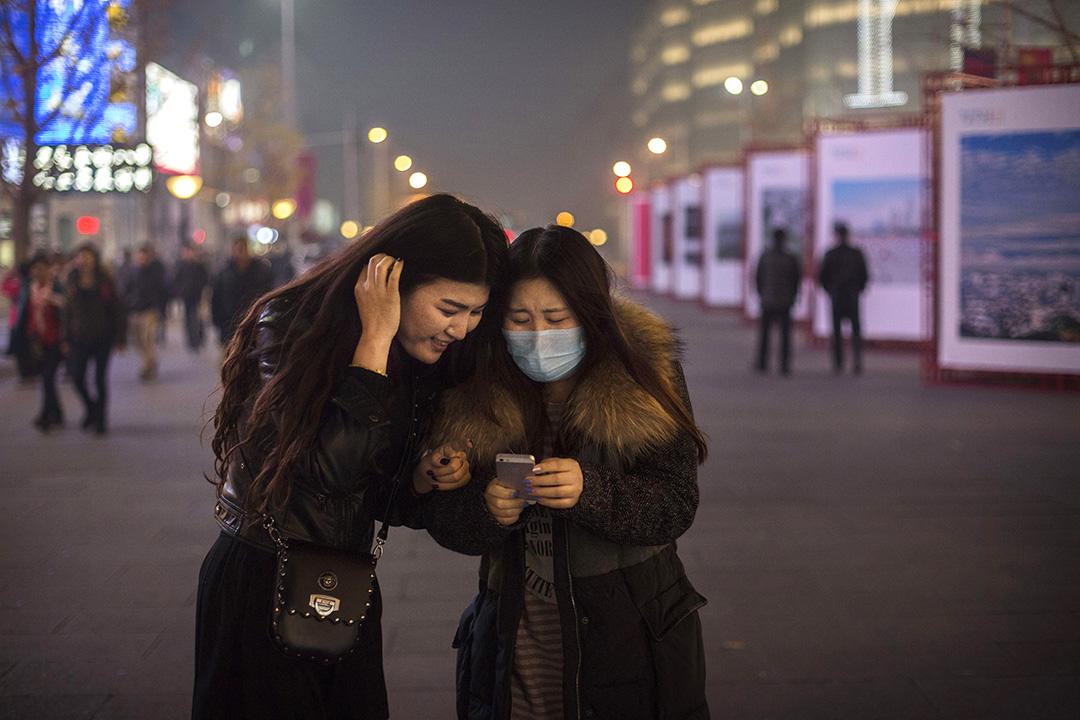 兩位女士在北京街頭低頭看手機上的信息。攝:Kevin Frayer/GETTY