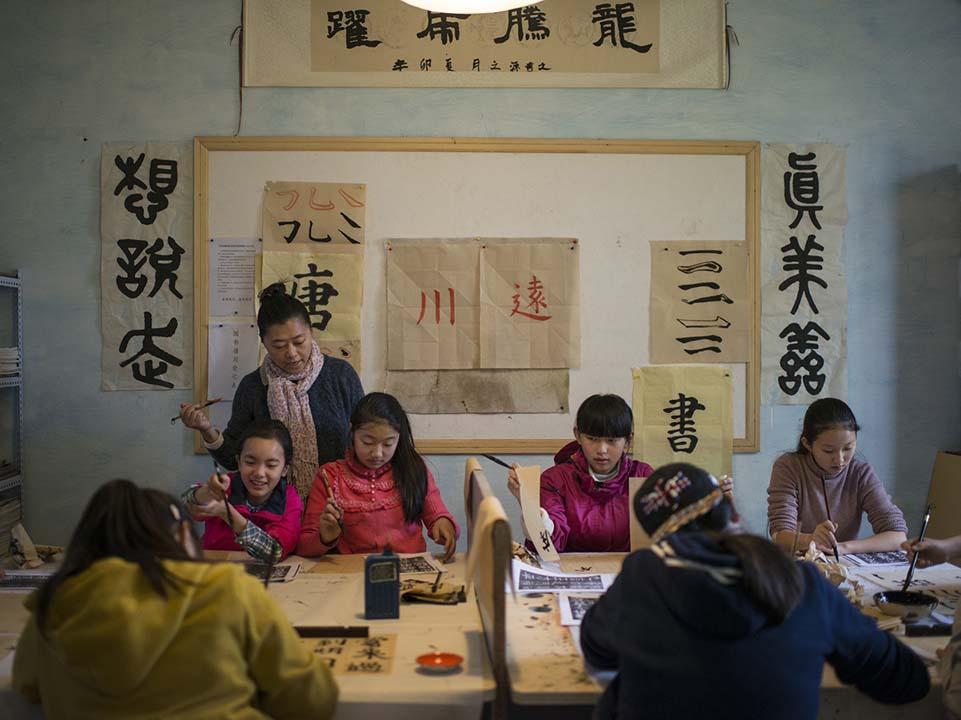 同學們在學毛筆字。攝:Wu Yue/端傳媒