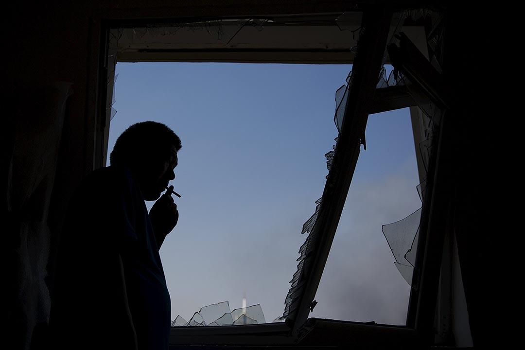 一名男子在玻璃完全震碎的居民樓里,緩緩吸菸,看向窗外的廢墟。