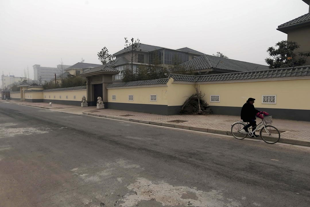 一名男子騎單車行經谷俊山的物業。攝 : Stringer/REUTERS