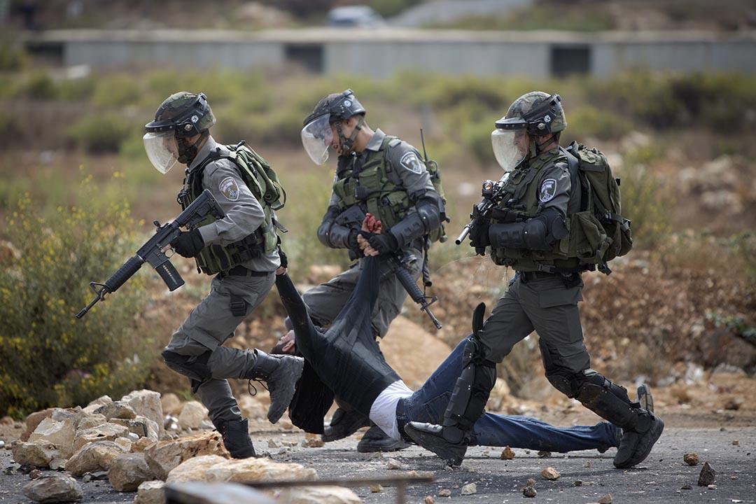 2015年10月7日,約旦河西岸城市拉姆安拉, 以色列軍人在衝突中攙扶一名受傷的巴勒斯坦男子。 攝:Majdi Mohammed/AP