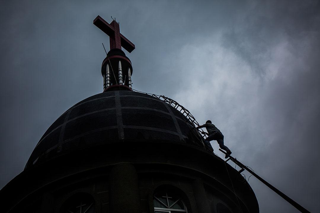 一名信信徒爬上平陽縣水頭鎮的一家教堂加固十字架,政府早前曾經派人清除這教堂十字架但不成功。 攝:Billy H.C. Kwok/端傳媒