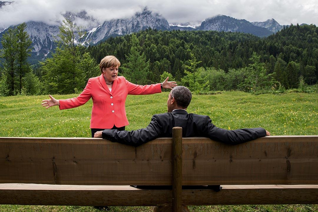 2015年6月8日,G7七國集團峰會期間,德國總理默克爾與坐在長椅上的美國總統奧巴馬傾談。攝:Michaek Kappeler/Pool Photo via AP