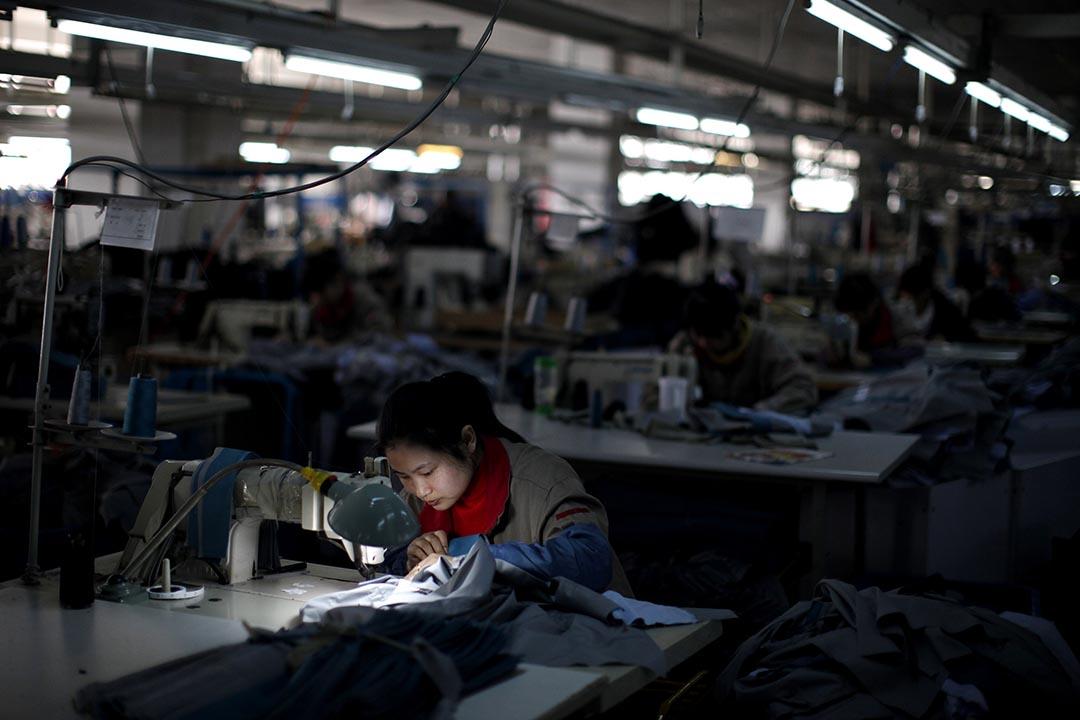 中國江蘇省一間製衣廠一名女工在工作。攝:Carlos Barria/REUTERS