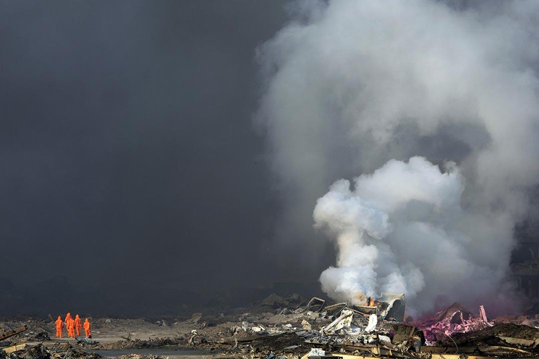 身著防護服的消防員注視着爆炸地點不斷升騰的濃煙。