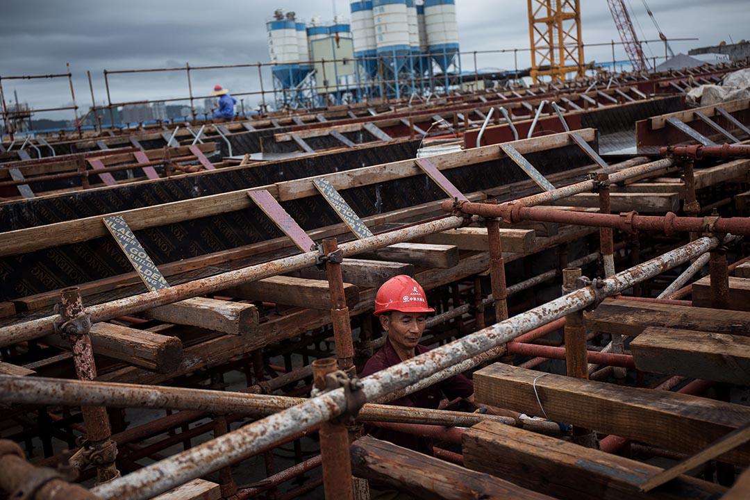 在港珠澳大橋的地盤裡,建築工人正在興建橋躉支架。