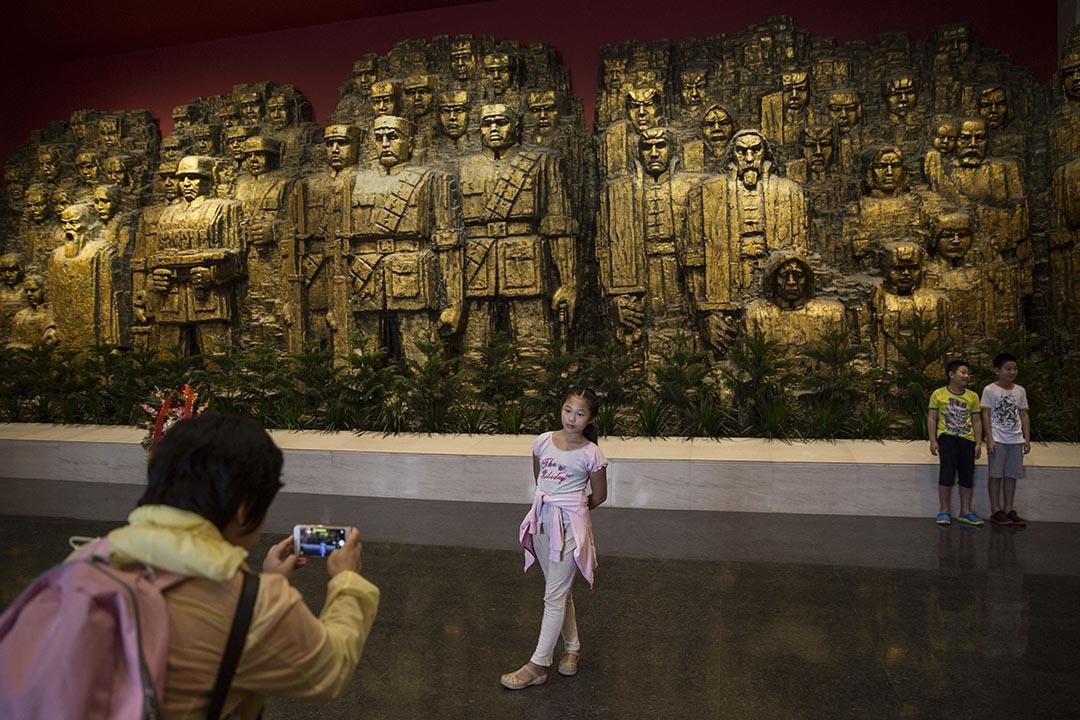 2015年9月1日,北京,一名女孩參觀中國人民抗日戰爭紀念館時在展品前拍照。攝:Kevin Frayer/GETTY