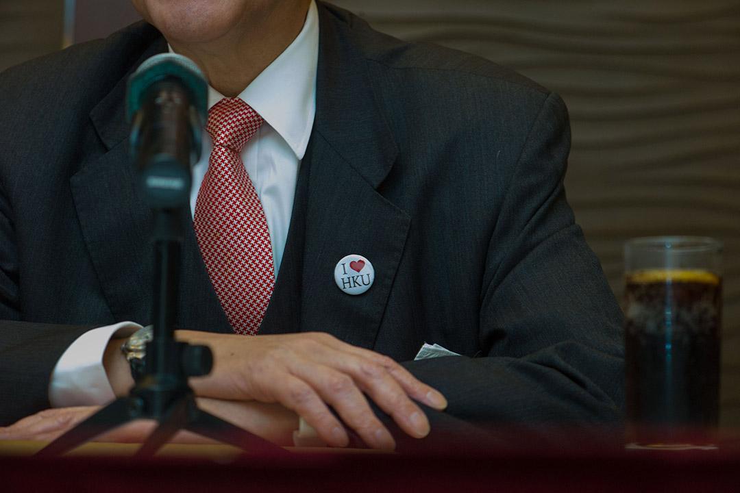 2016年1月28日,香港大學校委會主席李國章召開記者會譴責有學生在早前的校委會結束後包圍他,席間他戴上「我愛港大」襟章。攝:葉家豪/端傳媒