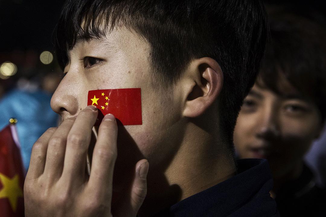 2015年10月1日,北京,中國66周年國慶日,一名在臉上畫上國旗的男子在天安門廣場等候觀看升旗禮。攝:Kevin Frayer/GETTY