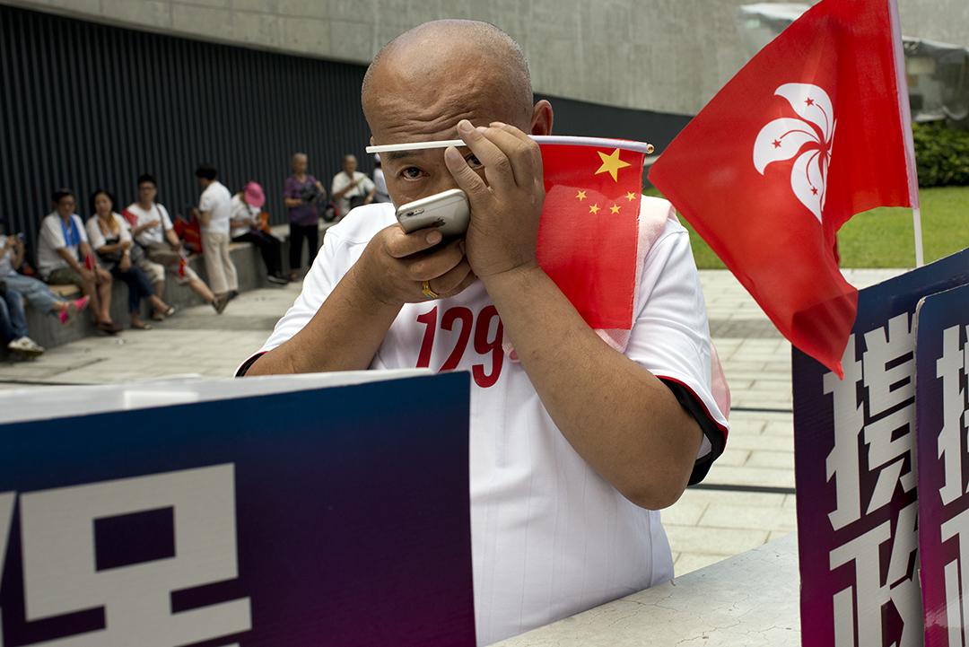 支持政改人士手持中國國旗,於今年6月政改表決當日在立法會外集會。攝:Eric Rechsteiner-Panos/端傳媒